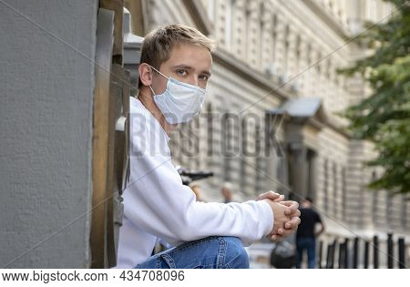 A Young Guy 20-25 Years Old In A Medical Mask With A Backpack Is Sitting On The Steps At The Entranc