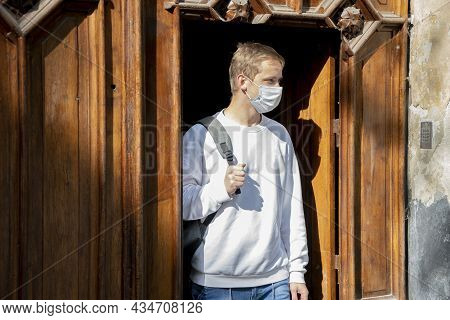 A Young Guy 20-25 Years Old In A Medical Mask And With A Backpack Comes Out Of The Wooden Doors. Con