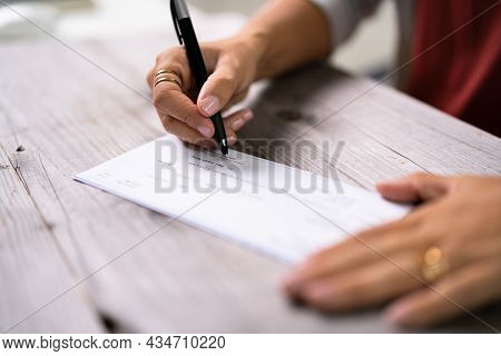 Writing Payroll Check. Hands Signing Cheque Document