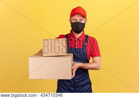 Courier In Blue Overalls Red T-shirt And Cap And Protective Mask Holding Cardboard Boxes, Express Pa