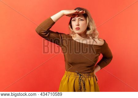 Portrait Of Curious Blonde Woman Holding Hand Above Eyes And Peering Into Distance, Looking Far Away