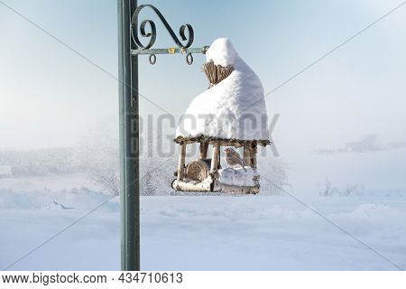 Beautiful Wooden Bird House With Roof Covered By Snow In Winter. An European Robin Is Sitting In The