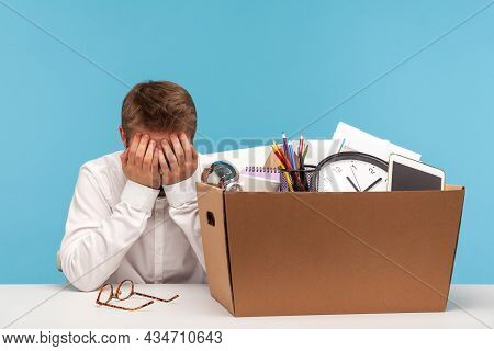 Depressed Fired Male Employee Crying Hiding Face, Leaving Office Workplace With Prepared Box Of Belo