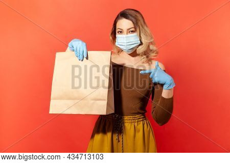 Shopping Safe, Stay At Home. Woman In Protective Mask And Gloves Pointing Paper Bag With Food, Purch