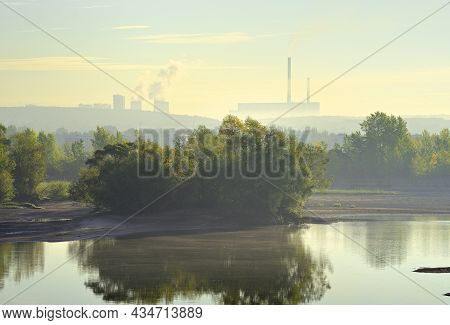 The Bank Of The Ob River In The Morning Fog. Chpp-5 Pipes In The Distance On The Horizon