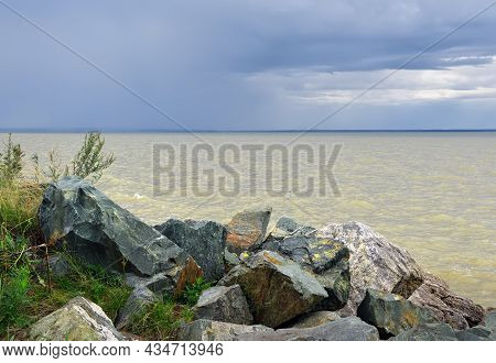 Large Stones On The Shore Of The Ob Sea, Waves On The Water Under A Blue Sky With Dramatic Cumulus C