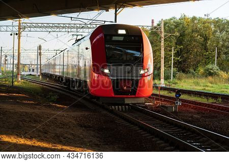 Modern Russian Intercity High Speed Train Under The Bridge At Sunset. Industrial Landscape With Pass