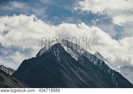 Atmospheric Alpine Landscape With High Mountain Silhouette With Snow On Peaked Top Under Blue Cloudy