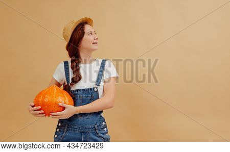 Young Farmer Woman In Overalls Holds A Ripe Orange Pumpkin On A Yellow Background. Concept Of Organi