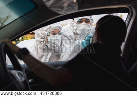 Medical Staffs With Ppe Use Infrared Thermometer Gun To Check Body Temperature At Drive Thru Station
