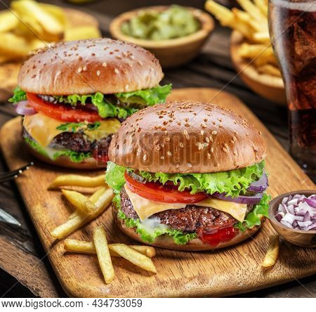 Delicious cheeseburger with cola and potato fries on the wooden background. Fast food concept.