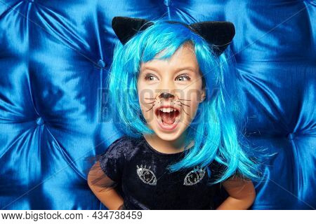 Cute cheerful little girl in a kitty costume and bright blue wig poses cheerfully screaming while having fun on Halloween party. Carnival kitty costume.