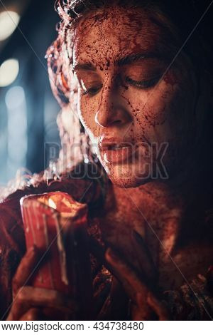 A girl drenched in blood stands in a dark room and looks at the candle in her hands. Horror, thriller. Halloween. Vampires.