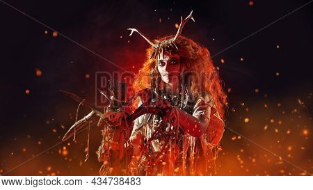 Portrait of a shaman woman wearing ritual clothes and holding a shaman staff in her hand surrounded by sparks from fire. Ethnic traditions. Paganism. Halloween.
