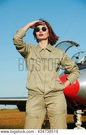 Confident female pilot stands in front of the plane and looks into the distance. Commercial and military aviation.