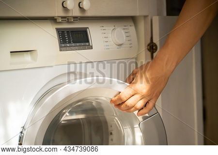 A Male Hand Opens The Door Of A New Washing Machine In His Modern, Bright Bathroom, Close-up. The Ma