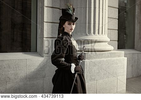 Portrait of an elegant 19th century lady strolling down a city street. History and Fashion of the late 19th - early 20th century.