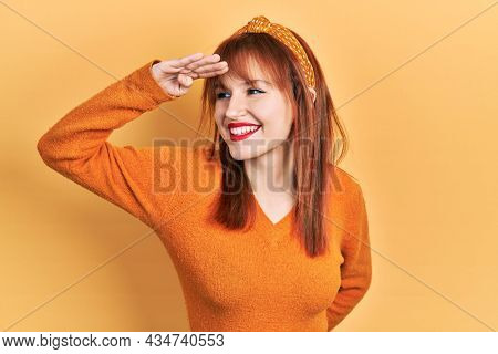 Redhead young woman wearing casual orange sweater very happy and smiling looking far away with hand over head. searching concept.