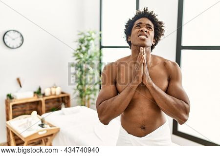 Young african american man shirtless wearing towel standing at beauty center begging and praying with hands together with hope expression on face very emotional and worried. begging.