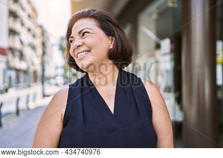 Middle age hispanic woman smiling happy and confident outdoors on a sunny day