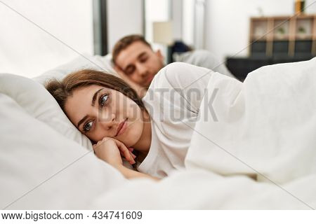 Young caucasian couple sleeping on bed at home.