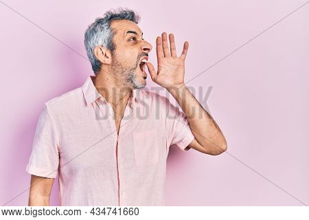 Handsome middle age man with grey hair wearing casual shirt shouting and screaming loud to side with hand on mouth. communication concept.