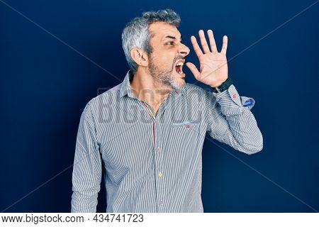 Handsome middle age man with grey hair wearing business shirt shouting and screaming loud to side with hand on mouth. communication concept.