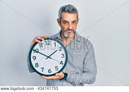 Handsome middle age man with grey hair holding big clock skeptic and nervous, frowning upset because of problem. negative person.