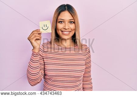 Beautiful hispanic woman holding smile emoji reminder looking positive and happy standing and smiling with a confident smile showing teeth