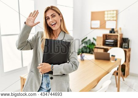 Blonde business woman at the office waiving saying hello happy and smiling, friendly welcome gesture