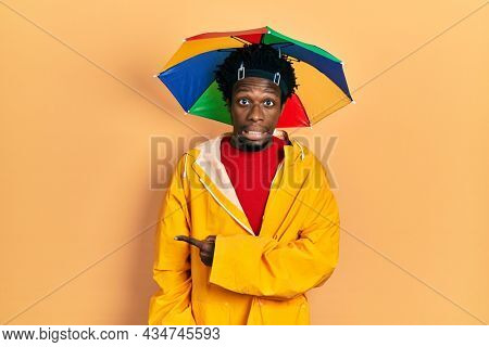 Young african american man wearing yellow raincoat pointing aside worried and nervous with forefinger, concerned and surprised expression