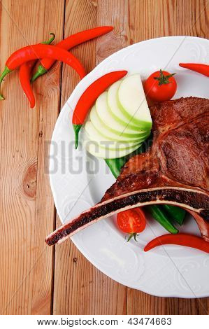 savory : roasted beef spare rib on white dish with cutlery thyme pepper and tomato on wooden table