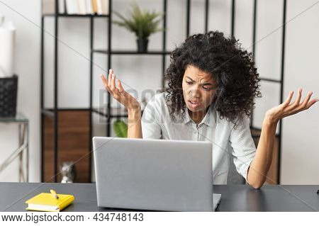 Confused African-american Businesswoman In Casual Shirt Sitting At The Desk In Front Of Laptop And S