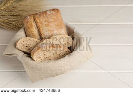 Cut Delicious Ciabatta In Wicker Basket On Beige Wooden Table, Space For Text