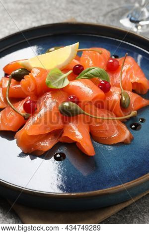 Salmon Carpaccio With Capers, Cranberries, Basil And Lemon On Grey Table, Closeup