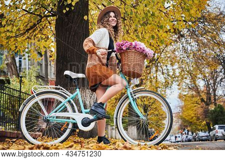 Autumn Bike Ride Through Town. Side View Of Beautiful Woman Cyclist With Curly Hair In Stylish Hat O