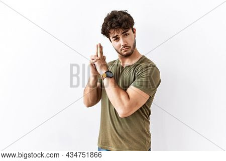 Hispanic man standing over isolated white background holding symbolic gun with hand gesture, playing killing shooting weapons, angry face