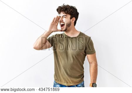 Hispanic man standing over isolated white background shouting and screaming loud to side with hand on mouth. communication concept.