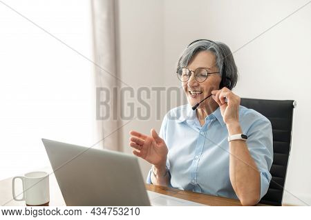 Grey-headed Mature Senior Female Office Worker Sitting At The Desk With A Laptop, Wearing Glasses, H