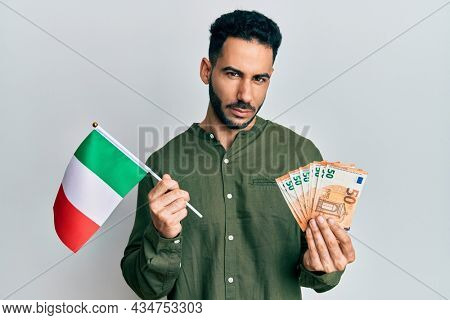 Young hispanic man holding italy flag and euros banknotes skeptic and nervous, frowning upset because of problem. negative person.