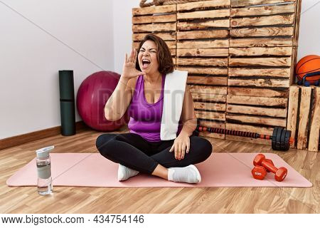 Middle age hispanic woman sitting on training mat at the gym shouting and screaming loud to side with hand on mouth. communication concept.