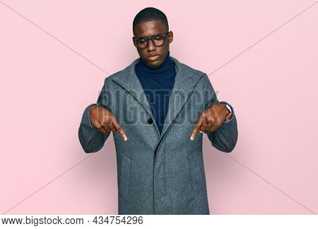 Young african american man wearing business clothes and glasses pointing down looking sad and upset, indicating direction with fingers, unhappy and depressed.