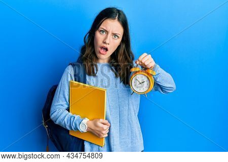 Young brunette student woman holding alarm clock in shock face, looking skeptical and sarcastic, surprised with open mouth
