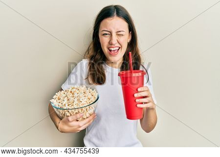 Young brunette woman eating popcorn and drinking soda winking looking at the camera with sexy expression, cheerful and happy face.