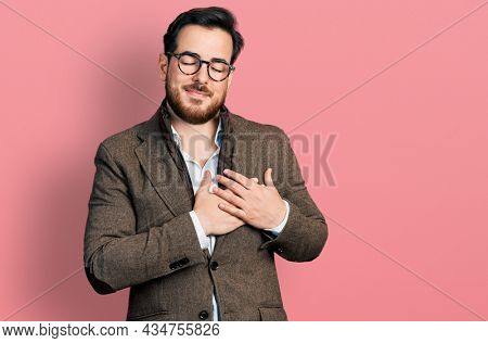 Young hispanic man wearing business jacket and glasses smiling with hands on chest with closed eyes and grateful gesture on face. health concept.