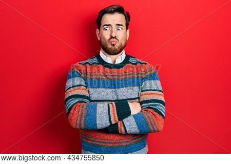 Handsome caucasian man with beard with arms crossed gesture making fish face with mouth and squinting eyes, crazy and comical.