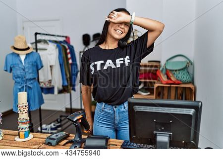 Young hispanic woman working as staff at retail boutique smiling cheerful playing peek a boo with hands showing face. surprised and exited