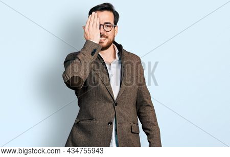 Young hispanic man wearing business jacket and glasses covering one eye with hand, confident smile on face and surprise emotion.