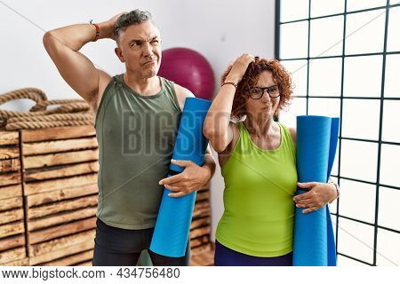 Middle age couple holding yoga mat confuse and wondering about question. uncertain with doubt, thinking with hand on head. pensive concept.
