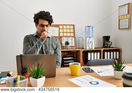Young hispanic man wearing business style sitting on desk at office feeling unwell and coughing as symptom for cold or bronchitis. health care concept.